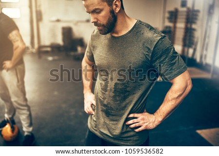 Fit young man in sportswear standing with his hands on his hips in a gym sweating after a workout session