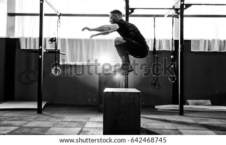 Stock Photo Fit young man jumping onto a box as part of exercise routine. Man doing box jump in the gym. Athlete is performing box jumps
