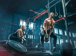 Fit young man lifting weight working out at a gym. Sport, fitness, weightlifting, bodybuilding, training, athlete, workout exercises concept
