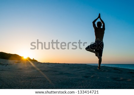 Fit young man practices sun salutation yoga on the beach at sunset #133414721