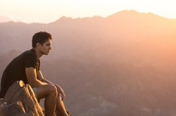 Fit young man sitting alone on top of a mountain at beautiful sunset.