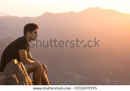 Fit young man sitting alone on top of a mountain at beautiful sunset.  Foto d'archivio ©
