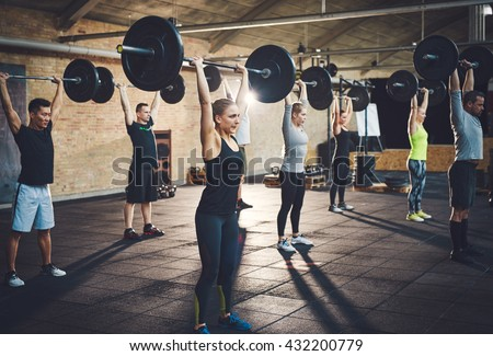 Fit young people lifting barbells looking focused, working out in a gym