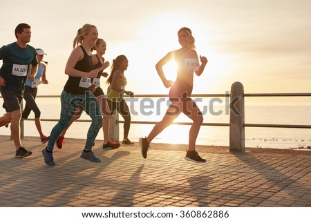 Fit young people running on street by the sea. Runners competing in a marathon race in evening.