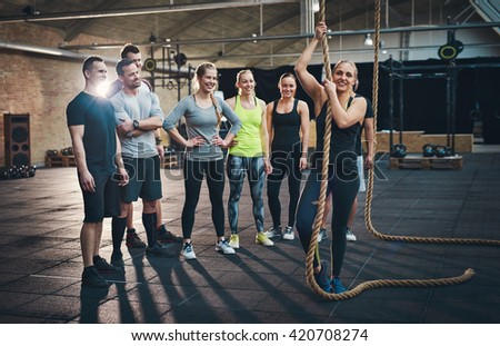 Fit young people standing around a rope in a gym looking positive