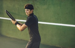 Fit young tennis player playing a game on hard court. Caucasian sportsman hitting a forehand on tennis court.