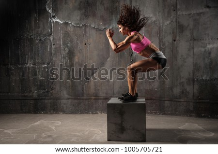 Fit young woman box jumping at a crossfit style on gray background. Fitness,  functional, training, and lifestyle concept