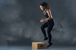 Fit young woman box jumping at a crossfit style on gray background with copy space. Fitness, crossfit, functional, training, and lifestyle concept