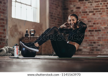 Fit young woman doing crunch workout to improve her abs. Smiling female in the gym doing sit-up exercise at gym.