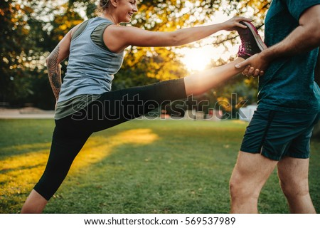 Shutterstock Fit young woman doing stretching exercises with the help of a personal trainer in park. Coach holding leg of female.