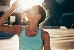 Fit young woman drinking water after workout session. Thirsty female athlete drinking water outdoors.