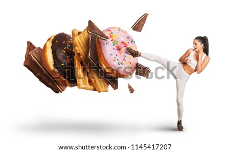 Fit young woman fighting off sweets and candy
