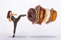 Fit young woman fighting off sweets and candy, Fit young woman saying NO to unhealthy carbohydrates