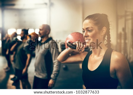 Fit young woman holding a dumbell while working out with other people during an exercise class at a gym