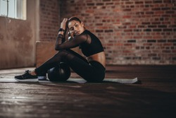 Fit young woman sitting on gym floor with medicine ball. Female resting after training session in healthclub.