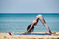 Fit young woman standing in downward facing dog to rest between difficult asanas
