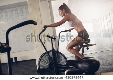 Fit young woman using exercise bike at the gym. Fitness female using air bike for cardio workout at crossfit gym.