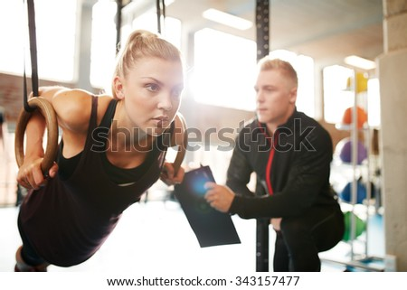 Fit young woman with her personal fitness trainer in the gym exercising with gymnastic rings