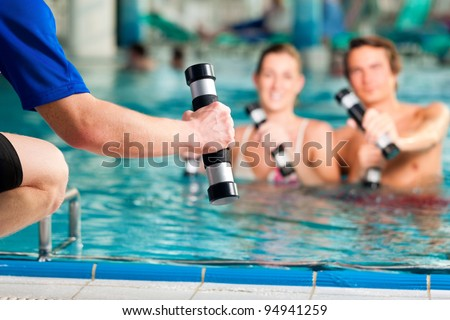 Fitness - a young couple (man and woman) doing sports and gymnastics or water aerobics under water in swimming pool or spa with dumbbells and instructor - stock photo