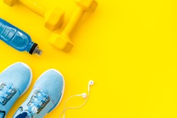 Fitness accessories. Dumbbells and sneakers on yellow table top view copy space
