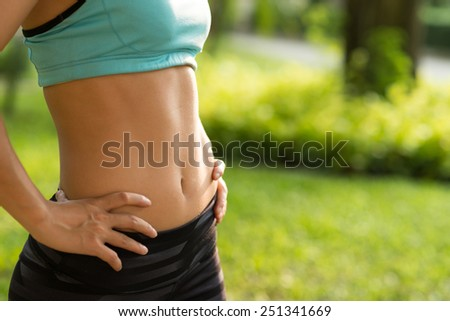 Fitness and diet concept: cropped image of woman in sportswear with perfect abs