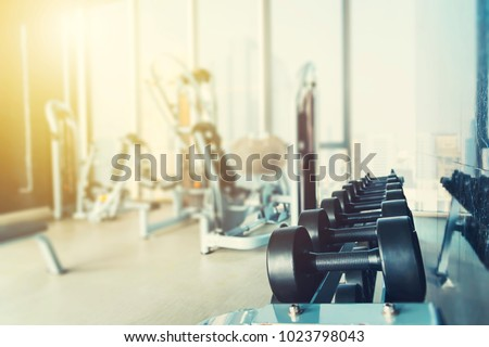 Fitness and healthy background concept. Dumbbells with blurred gym or sport club background at sunset. Picture for add text message. Backdrop for design art work.