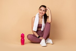 Fitness And Healthy Lifestyle Concept. Happy sporty young woman sitting on the floor with bottle of water at studio after exercising, resting and looking at camera. Wellness And Training