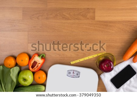 Fitness and weight loss concept, dumbbells, white scale, fruit and tape measure on a wooden table, top view, free copy space