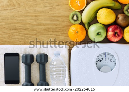 Fitness and weight loss concept, dumbbells, white scale, towel, fruit and mobile phone on a wooden table, top view