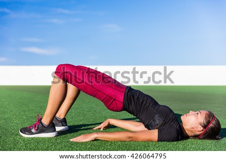 Fitness Asian woman doing bodyweight glute exercises with floor bridge hip raise butt life leg exercise outdoor grass gym. Healthy lifestyle strength training workout in activewear.
