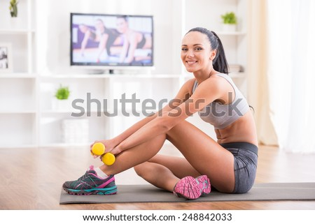 Fitness at home concept. Smiling young woman is sitting on mat with sports equipment at home.