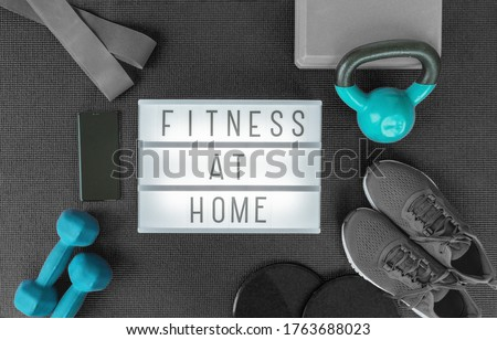 Fitness at home strength training program with dumbbells weights, resistance bands for cross fit workout on exercise mat .Top view of lightbox sign with black grey equipment.