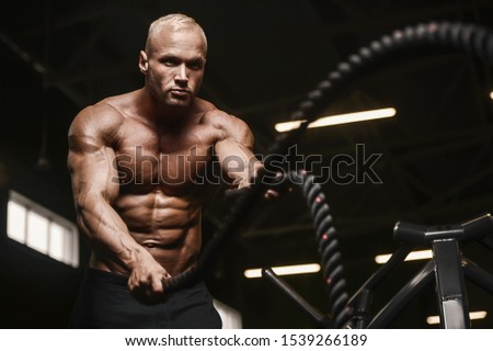 fitness athletes training using battle ropes intense workout team exercise challenge in gym enjoying healthy bodybuilding endurance practice lifestyle together