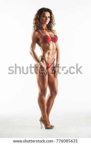 Fitness athletic woman in red bikini showing muscles. Isolated on white background #776085631