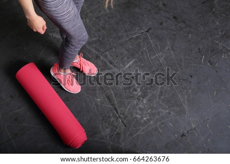 Fitness background, copy space, sport urban style, slim female legs, yoga mat, gray background