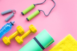 Fitness background. Equipment for gym and home. Jump rope, dumbbells, expander, mat, water on pastel pink background top view copy space