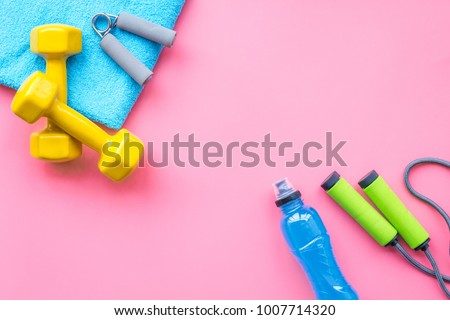 Fitness background. Equipment for gym and home. Jump rope, dumbbells, expander, water on pastel pink background top view copy space