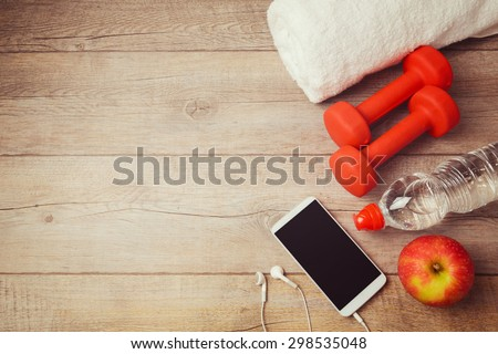 Fitness background with bottle of water, dumbbells and smartphone. View from above