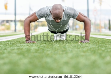 Fitness black man exercising push ups listening to music with headphones. Male model cross-training in urban background. African guy in his twenties doing workout outdoors in the street. #561813364