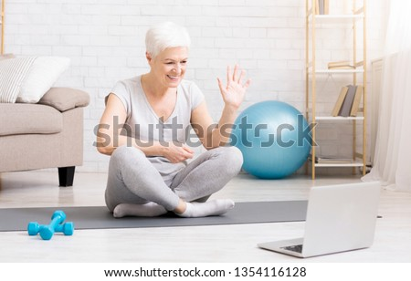 Fitness blog. Sporty mature woman showing her training online via laptop, preparing special workout plan for senior people, free space