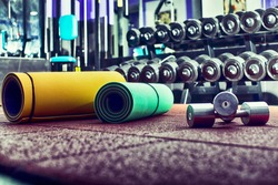 Fitness center interior. Closeup of dumbbells in gym.