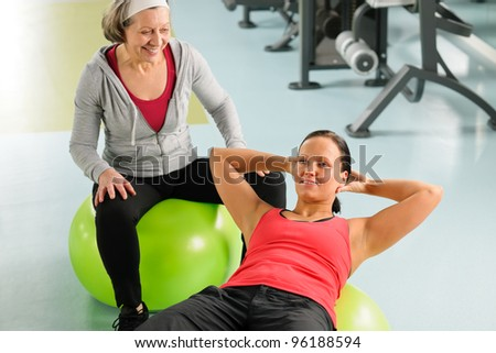 Fitness center senior woman with trainer exercising on swiss ball