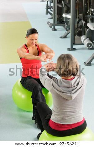 Fitness center senior woman with trainer stretching on swiss ball