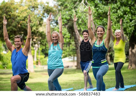 Fitness class stretching in the park - Shutterstock ID 568837483