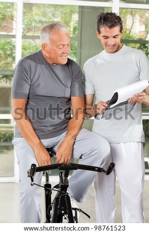 Fitness coach explaining training plan to senior man in gym