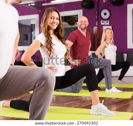 Fitness coach showing to adult learners new exercise at class