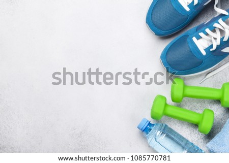 Fitness concept background with sneakers, dumbbells, water bottle and towel. Top view with space for your text