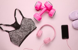 Fitness concept. Flat lay of a smartphone with headphones, plastic dumbbells, sports bra, sneakers on pink background. Top view