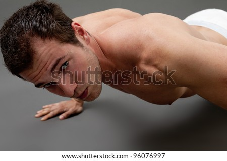 Fitness concept - sexy muscular man doing push-ups
