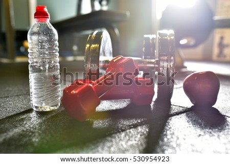 Fitness concept with dumbbells, water and apple